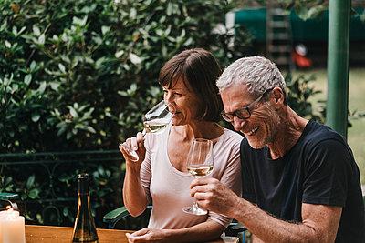 Reifes Paar im Garten trinkt Wein - p586m1178432 von Kniel Synnatzschke