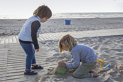 Brother and sister playing with sand at the beach - p896m1478937 by Amaury Miller
