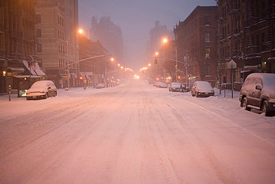 Cars parked on snowy city street - p924m807275f by REB Images