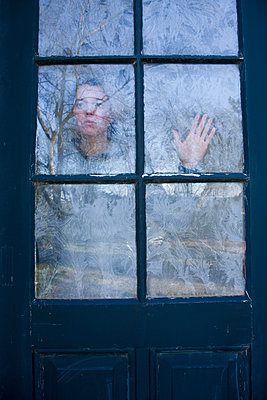 Woman looking through the windows which are covered with frost flowers - p1231m1043095 by Iris Loonen