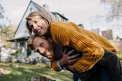Man giving his wife a piggyback ride in garden - p300m2166663 by Kniel Synnatzschke