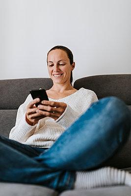 Happy woman using phone on sofa at home - p300m2240192 by David Molina Grande