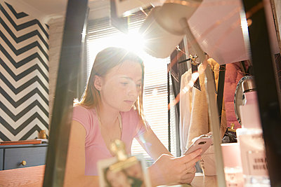 Teenage girl sitting in her room at a desk, doing checking her mobile phone. - p429m2200768 by Emma Kim