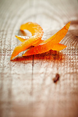 Orange curls on a wooden table - p968m658847 by Roberto Pastrovicchio