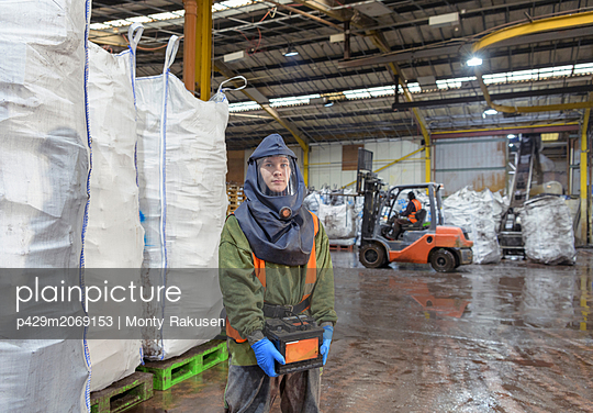Portrait of worker in vehicle battery recycling plant - p429m2069153 by Monty Rakusen