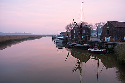 Sailing boats moored at harbour wall, reflected on the surface of a calm canal at twilight. - p1100m1575752 by Mint Images