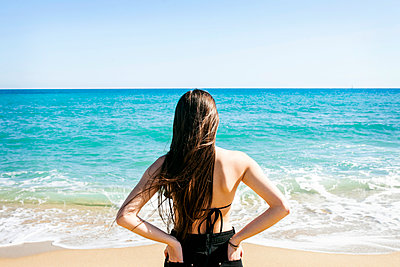 Rear view of young woman standing at beach against clear sky - p1166m1473674 by Cavan Images