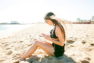 Side view of young woman using phone while sitting at beach against clear sky - p1166m1473680 by Cavan Images