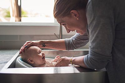 Side view of happy mother bathing cute son in kitchen sink at home - p1166m2067820 by Cavan Images