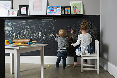 Brother and sister drawing on blackboard wall in playroom - p1192m1511071 by Hero Images