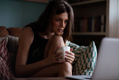 Young woman sittind on the sofa holding mug while looking at laptop - p1315m1186410 by Wavebreak