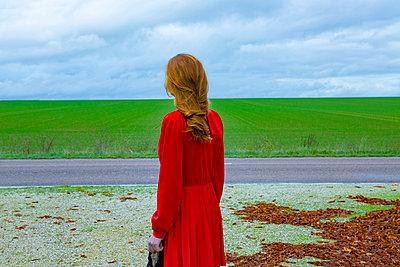 Frau in rotem Kleid an einer Straße - p1413m2221826 von Pupa Neumann