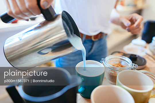 Close-up of woman pouring drink into cup - p300m1587371 by Bonninstudio