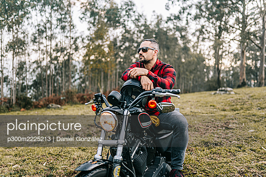 Male biker wearing sunglasses sitting on motorcycle in forest - p300m2225213 by Daniel González