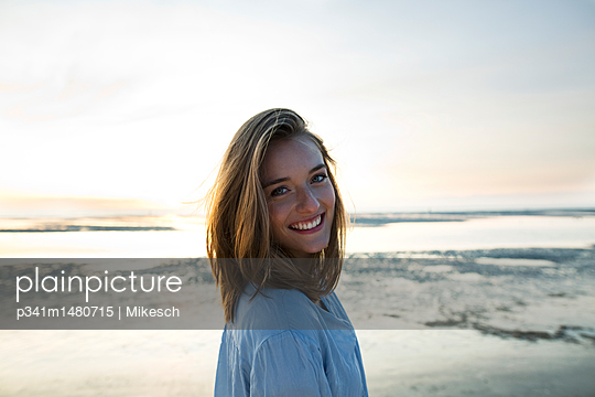 Happy young woman at sunset right beside the sea - p341m1480715 by Mikesch