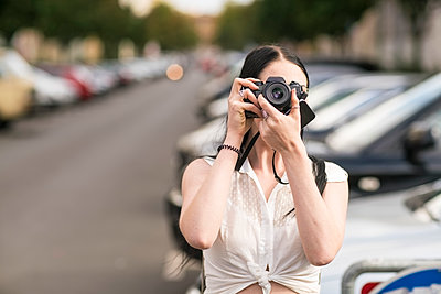 Young woman takes a picture with reflex camera  - p1332m1540015 by Tamboly
