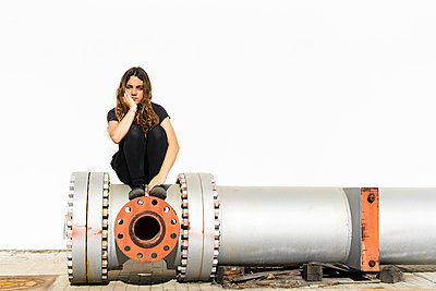 Portrait of serious teenage girl sitting on large pipe - p300m2102900 von Eloisa Ramos