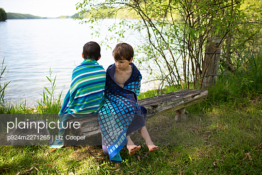 Canada, Ontario, Boys (6-7, 8-9) wrapped in towels after swimming - p924m2271265 by Liz Cooper