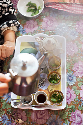 Pouring tea into tea glasses - p1167m2269965 by Maria Schiffer
