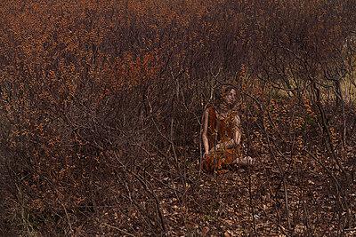 Junge Frau verträumt inmitten von Sträuchern - p1491m2108519 von Jessica Prautzsch