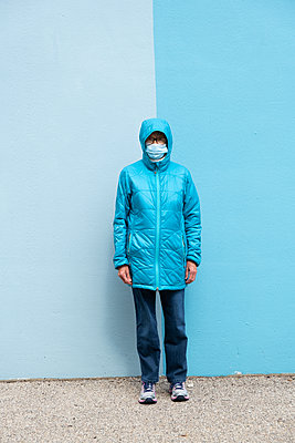 Portrait of woman in blue jacket and mask - p1614m2211827 by James Godman