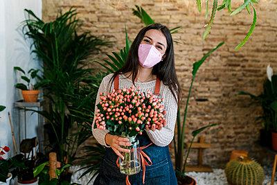Young female florist with protective face mask holding Hypercium flower vase at shop - p300m2274934 by Ezequiel Giménez