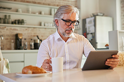 Businessman with digital tablet having coffee at office cafeteria - p300m2300433 by Rainer Berg