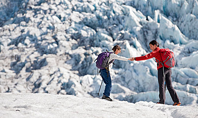 Mother and daughter walking on glacier - p429m727000f by Henn Photography
