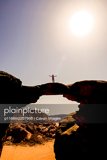 A Bedouin man poses atop a rock arch in Wadi Rum, NJordan - p1166m2207968 by Cavan Images