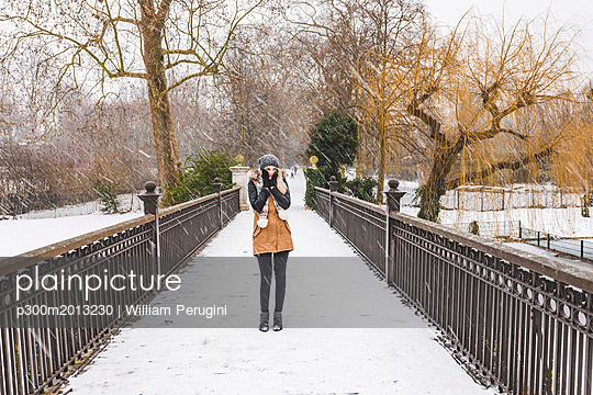 Teenage girl standing on footbridge in a park on a snowy day - p300m2013230 von William Perugini