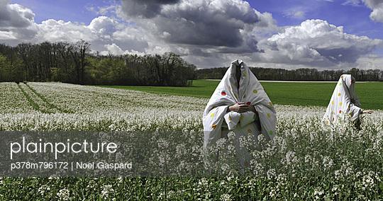 Covered men in field - p378m796172 by Noel Gaspard