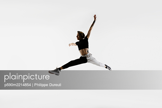 A dancer jumping in front of a white background - p590m2214854 by Philippe Dureuil
