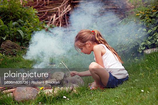 Littler girl sits by campfire - p896m835736 by Richard Brocken