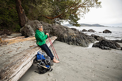 Thoughtful active senior man backpacking, resting on rugged beach - p1192m2000405 by Hero Images