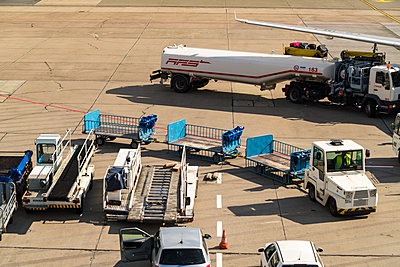 Road tanker and luggage carts on runway - p1332m1445877 by Tamboly