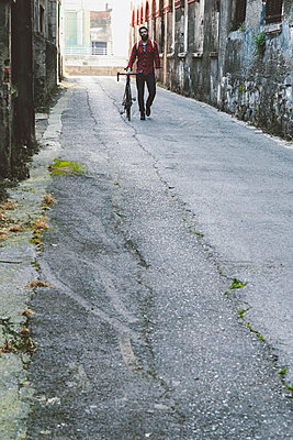 Spain, Bilbao, man with racing cycle walking in an alley of old industrial area - p300m1129874f von Retales Botijero