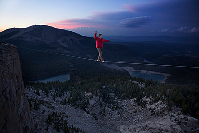 Male highliner walks a 125 foot highline over lakes in a gap on top of Mammoth Crest  - p343m1003004f by Jared Alden
