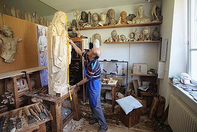 Sculptor measuring wooden figure - p429m747164f by Stefano Gilera