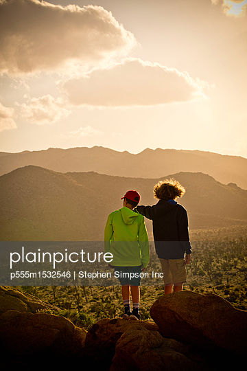 Boys standing on rock admiring desert landscape - p555m1532546 by Stephen Simpson Inc