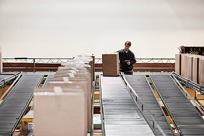 Caucasian warehouse worker in a large distribution warehouse, showing products stored in cardboard boxes, and moving on a motorized conveyor system. - p1100m1575469 by Mint Images