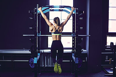 Rear profile of young woman doing chin ups at fitness centre - p1166m2095497 by Cavan Images