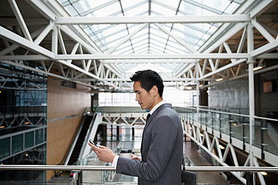 Businessman using smart phone on office atrium balcony - p1192m2093820 by Hero Images