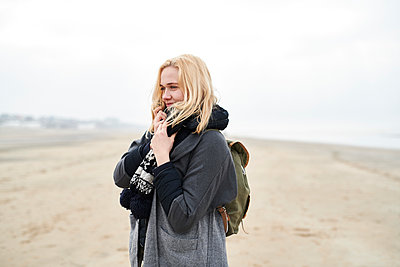 Portrait of blond young woman with backpack on the beach in winter - p300m1587050 by Markus Mielek