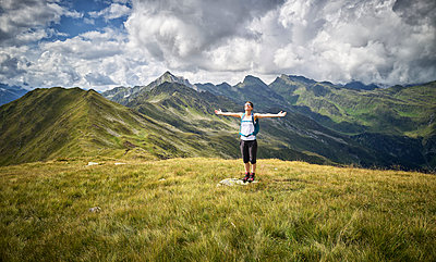 Cheerful woman having a break from hiking standing on alpine meadow, Passeier Valley, South Tyrol, Italy - p300m2154755 by Dirk Kittelberger