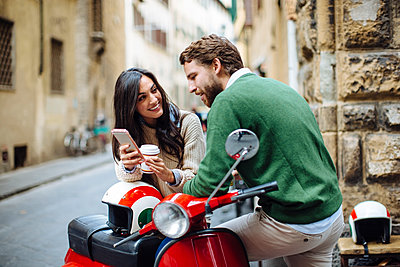 Smiling woman showing smart phone to boyfriend while leaning on Vespa - p300m2203024 by Sofie Delauw