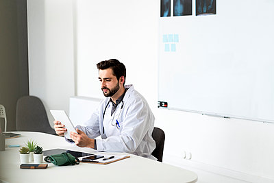 Handsome male doctor using tablet sitting at desk in hospital - p300m2275472 by Giorgio Fochesato
