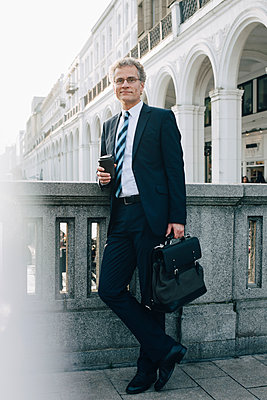 Portrait of confident businessman with disposable cup standing by retaining wall in city - p426m2186679 by Maskot