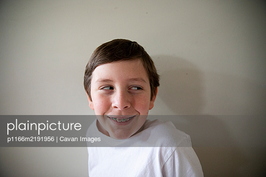Close Up Portrait of Tween Boy With Braces Smiling Looking Off Camera - p1166m2191956 by Cavan Images