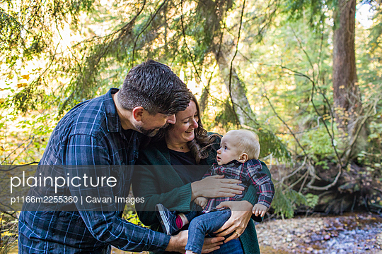 Mother and father bonding with their son outdoors. - p1166m2255360 by Cavan Images