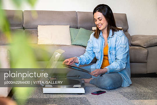 Smiling woman with turntable holding record while sitting by sofa at home - p300m2264430 by VITTA GALLERY